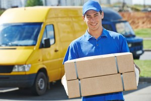 Smiling young male postal delivery courier man in front of cargo